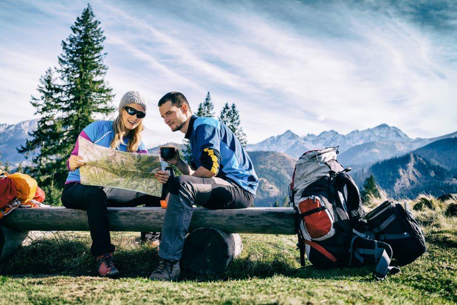para siedzi w górach na ławce i studiuje mapę