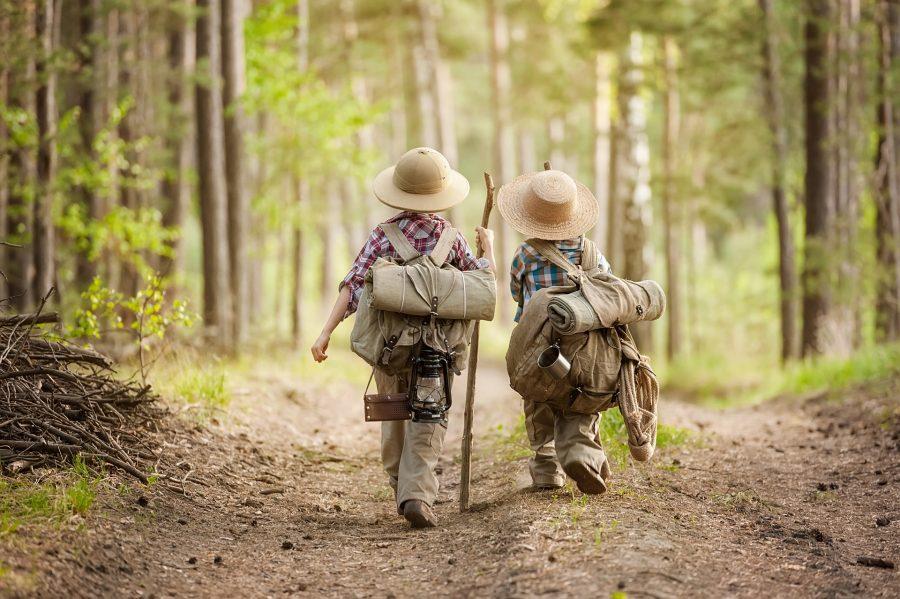 dzieci z plecakami idące na wakacje w lesie