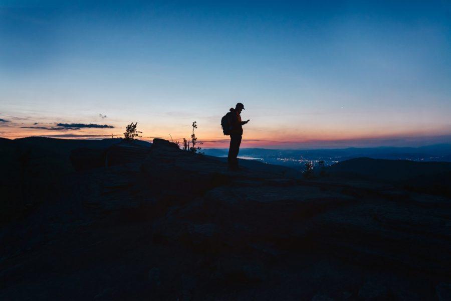 mężczyzna stoi w górach o zachodzie słońca