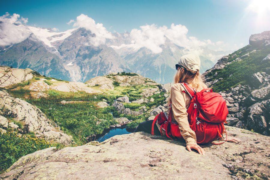 dziewczyna siedzi z plecakiem patrząc w góry