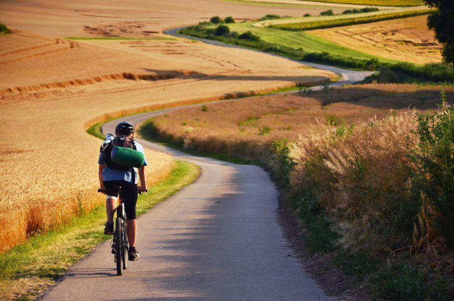 rowerzysta jadący polami wie jak się spakować na wakacje w Polsce